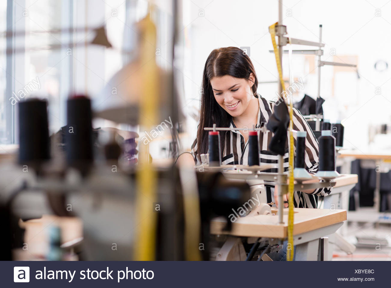 Young female seamstress using sewing machine in workshop - Stock Image