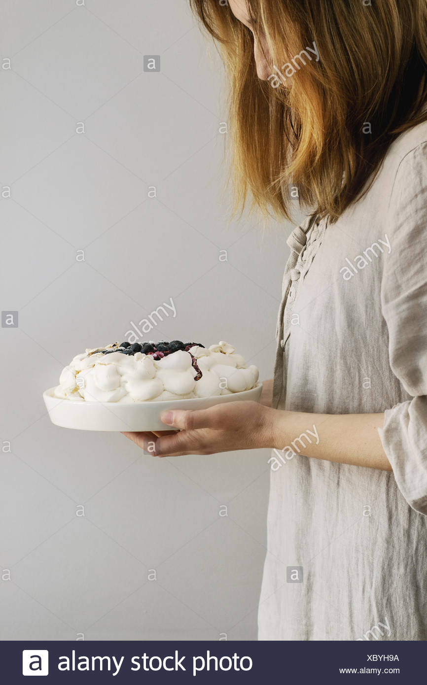 Woman tasting cake. Homemade meringue cake Pavlova with whipped cream, sugar powder, fresh blueberries and blueberry sauce in female hands over gray w - Stock Image
