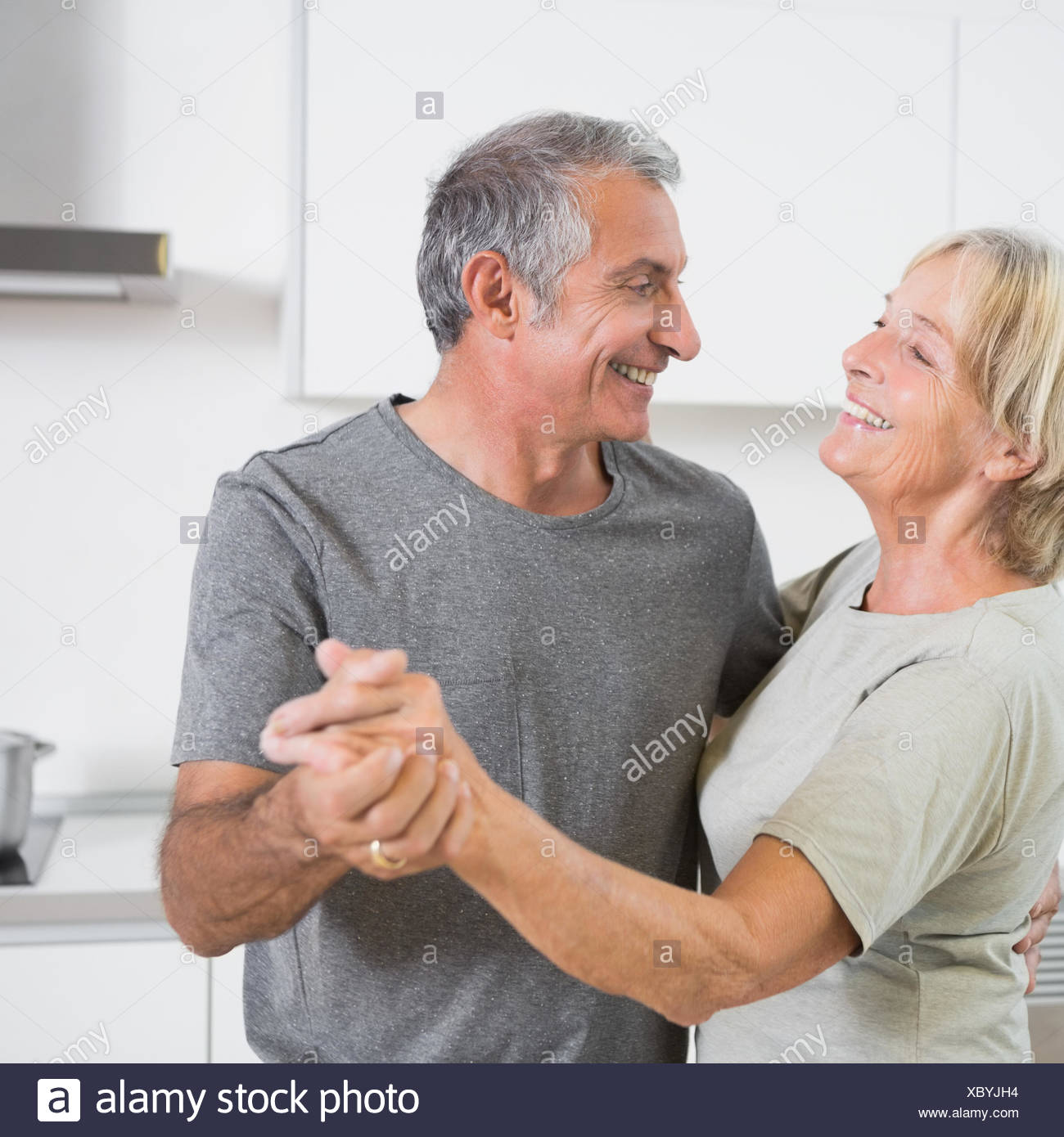 Smiling mature couple dancing together - Stock Image