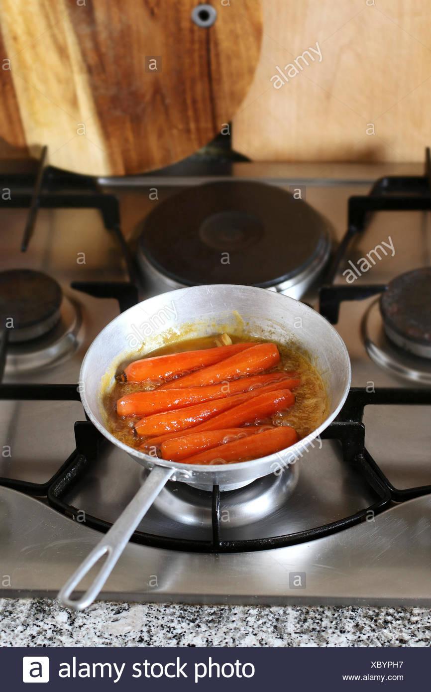 Honey glazed Carrots in pan simmering in freshly squeezed orange juice to glaze - Stock Image