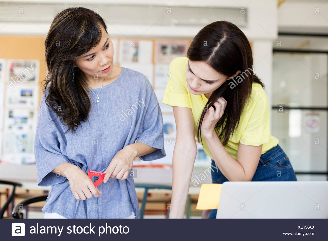 Teacher and student discussing work - Stock Image