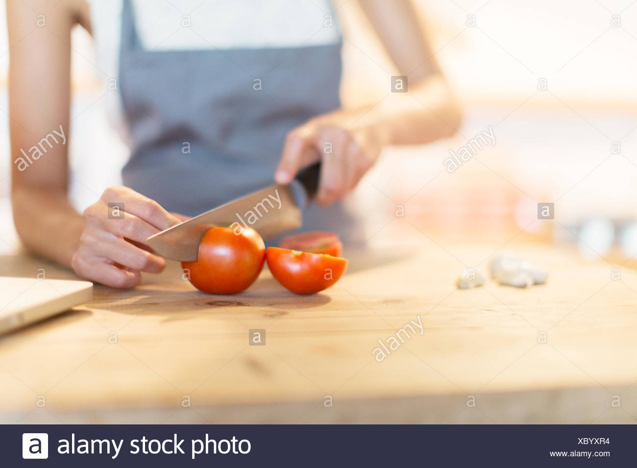 Woman chopping vegetables in kitchen - Stock Image