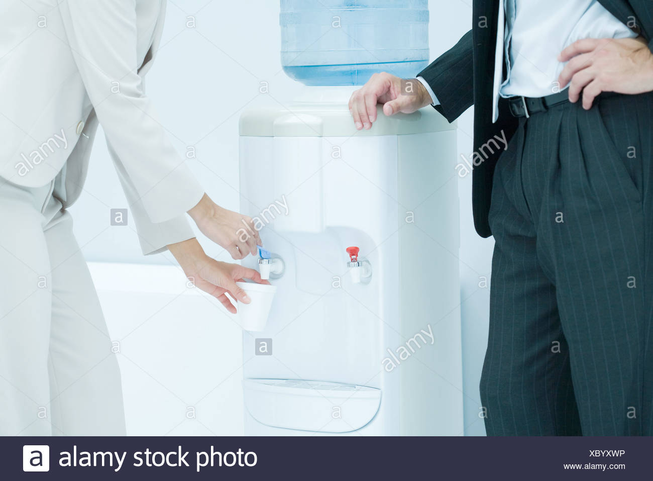 Professional woman filling disposable cup with water from water cooler, male colleague standing nearby, cropped view - Stock Image
