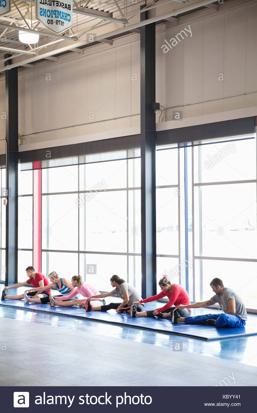 Group of people stretching in fitness class - Stock Image