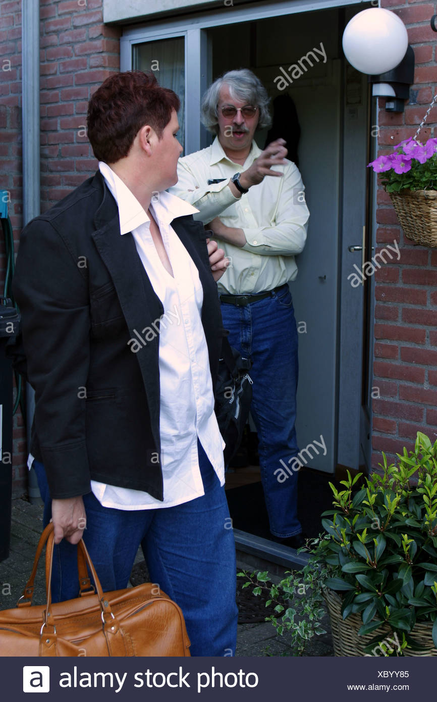 Woman leaving husband at a fight with luggage - Stock Image