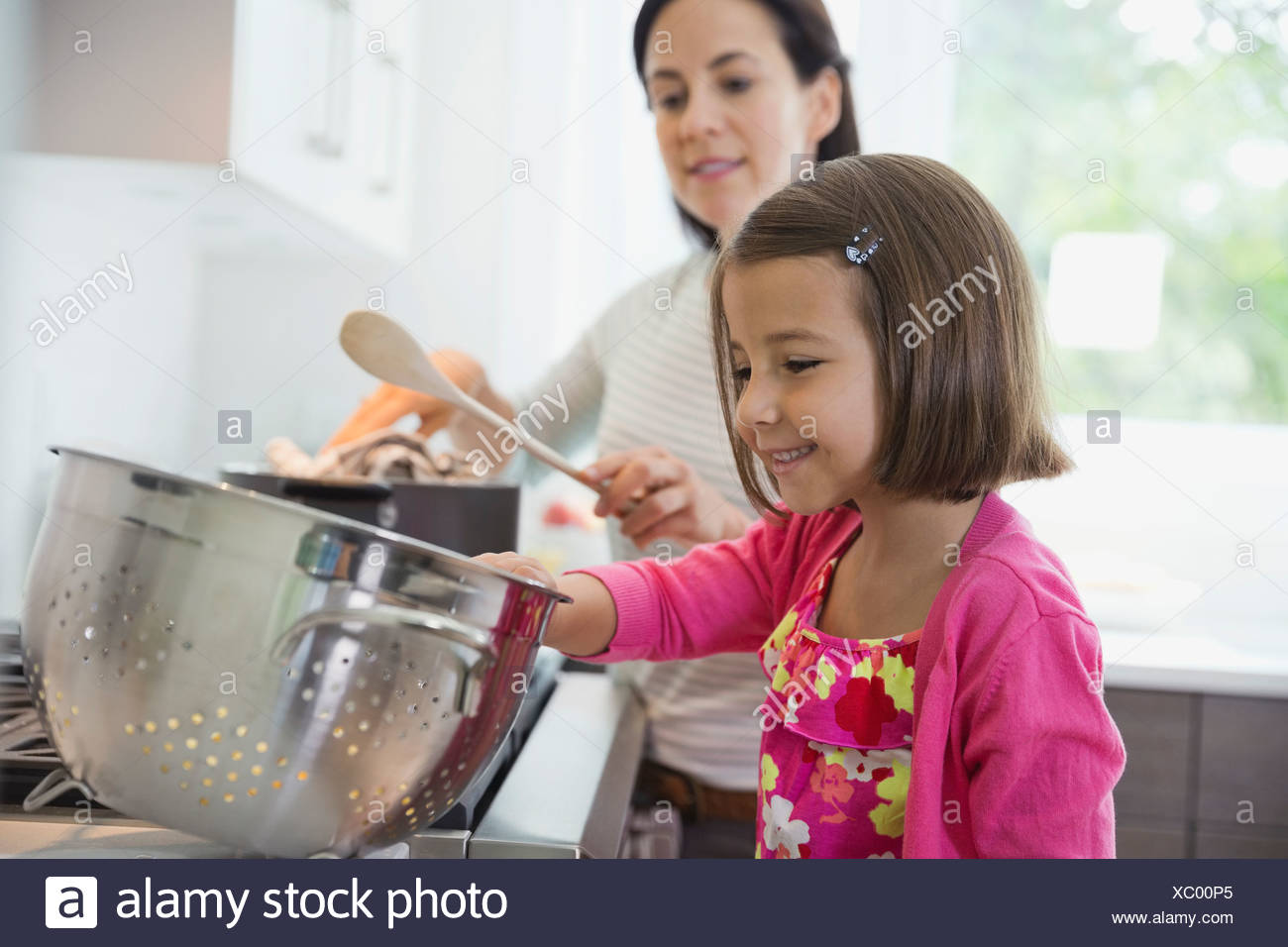 Mother and daughter cooking in kitchen - Stock Image