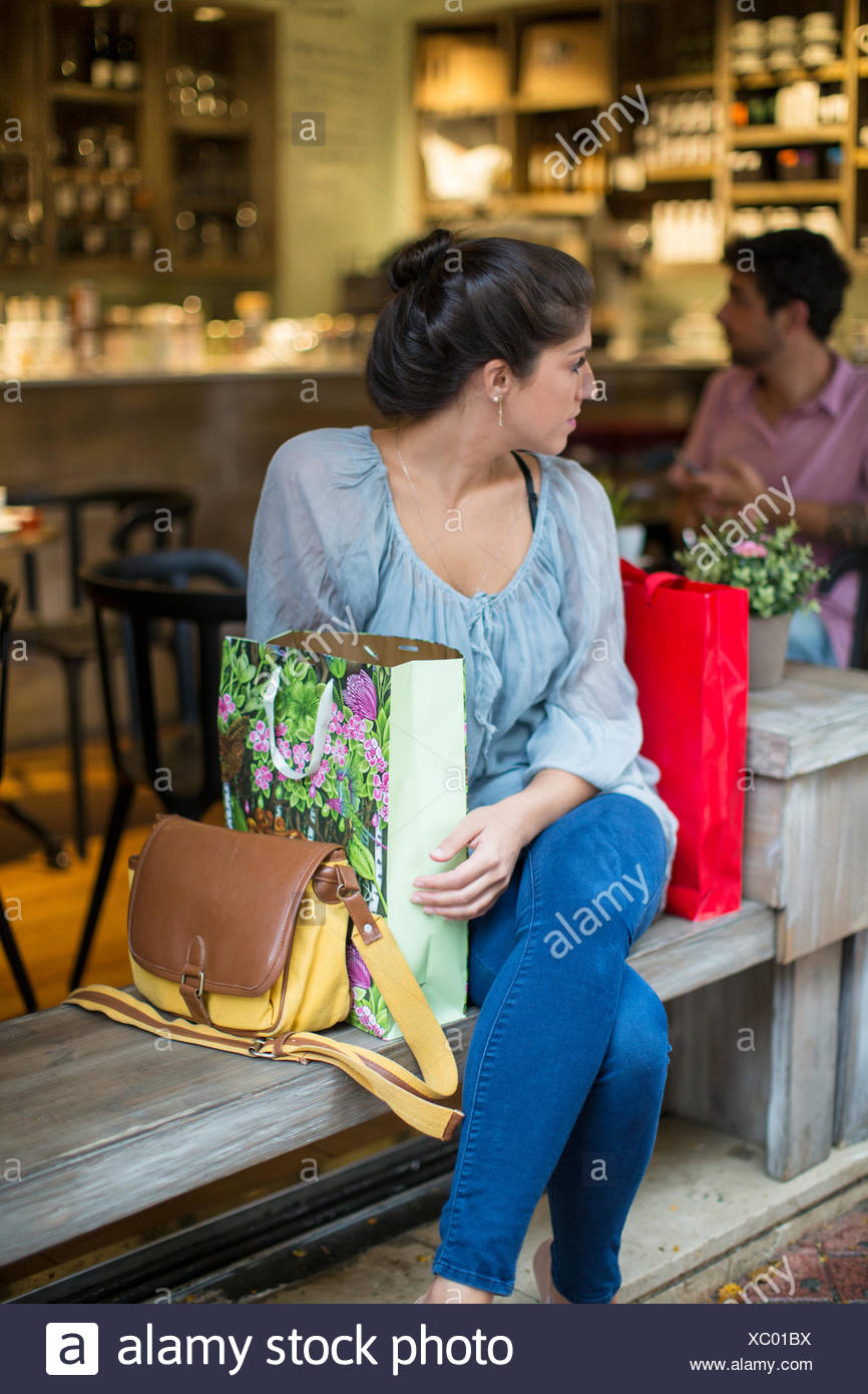Young woman shopper sitting outside cafe looking over her shoulder - Stock Image