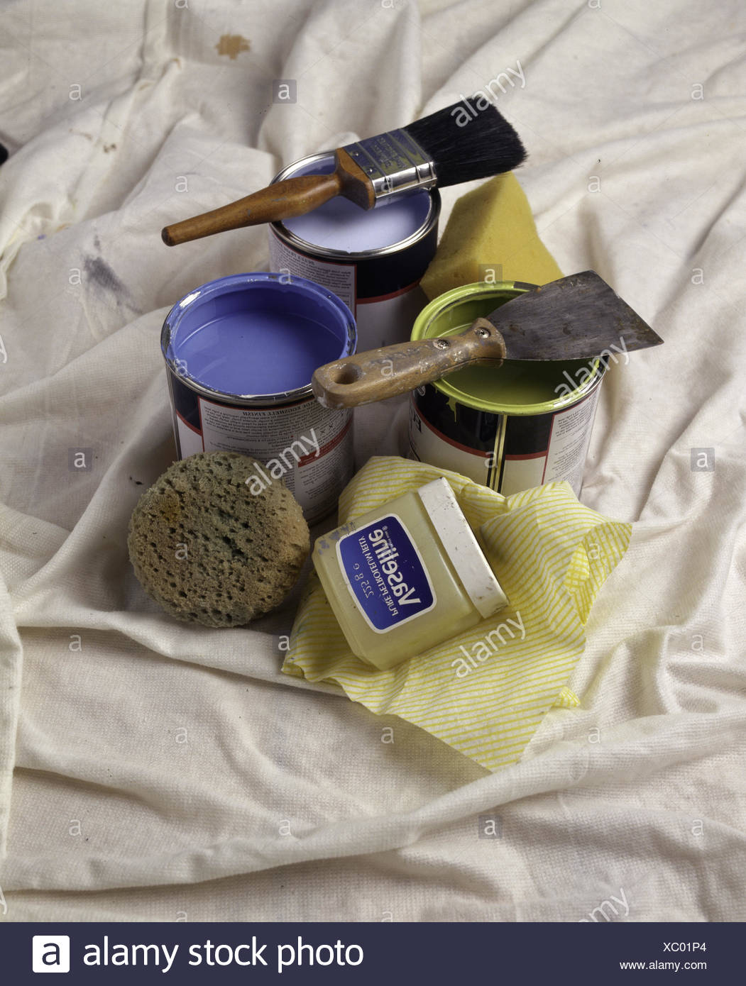 Tins of blue and green paint sith paint brushes - Stock Image