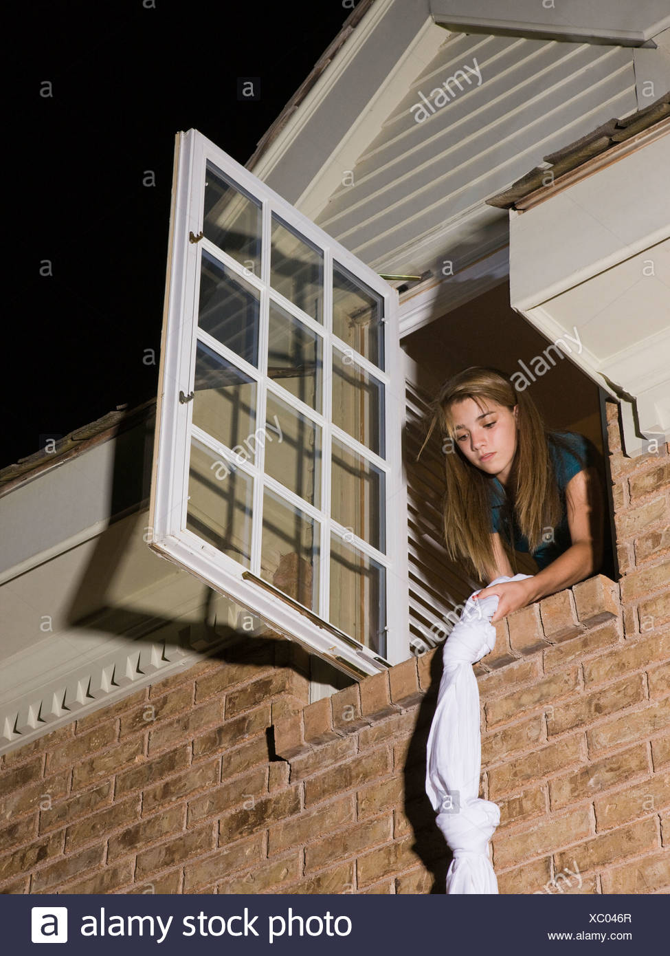 teenager climbing out of her bedroom window - Stock Image
