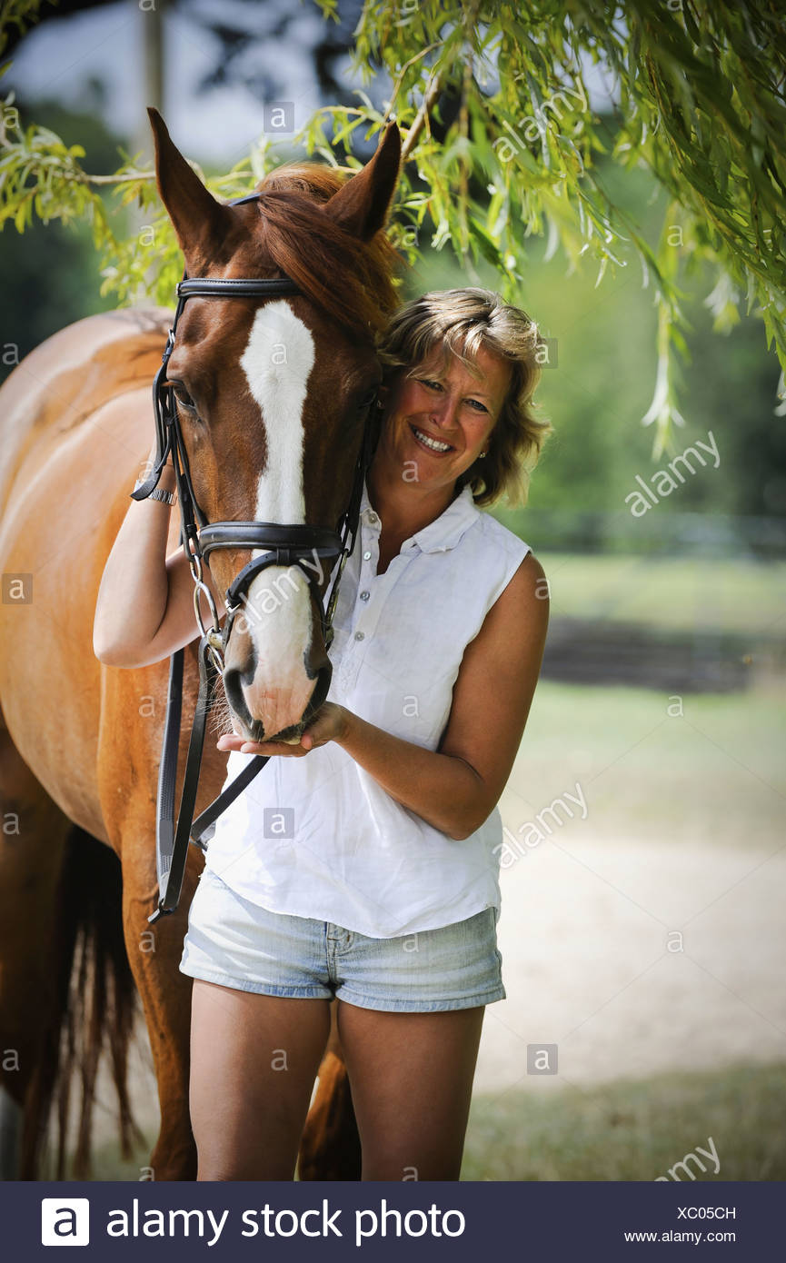 A woman standing next to a bayhorse with a halter rein  England - Stock Image