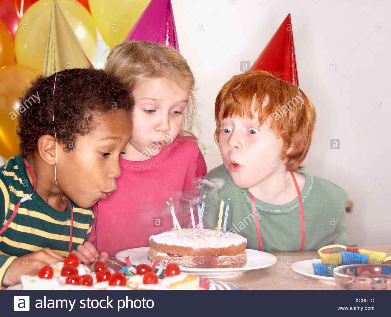 Three kids at a birthday party blowing out candles on cake - Stock Image