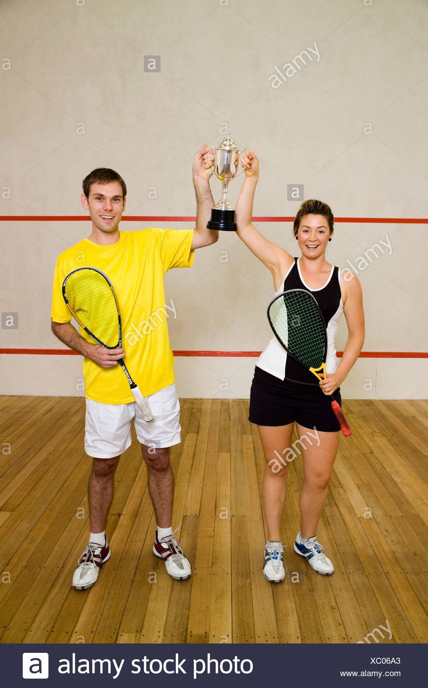 Two squash team mates holding a trophy - Stock Image