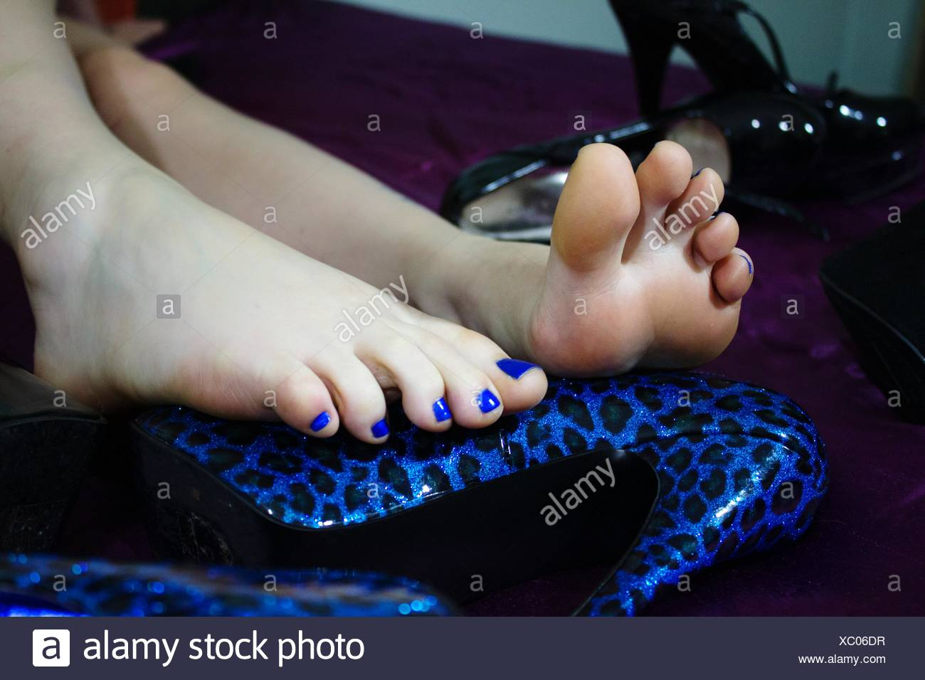 Low Section Of Woman With Blue Nail Polish Resting On Stiletto - Stock Image