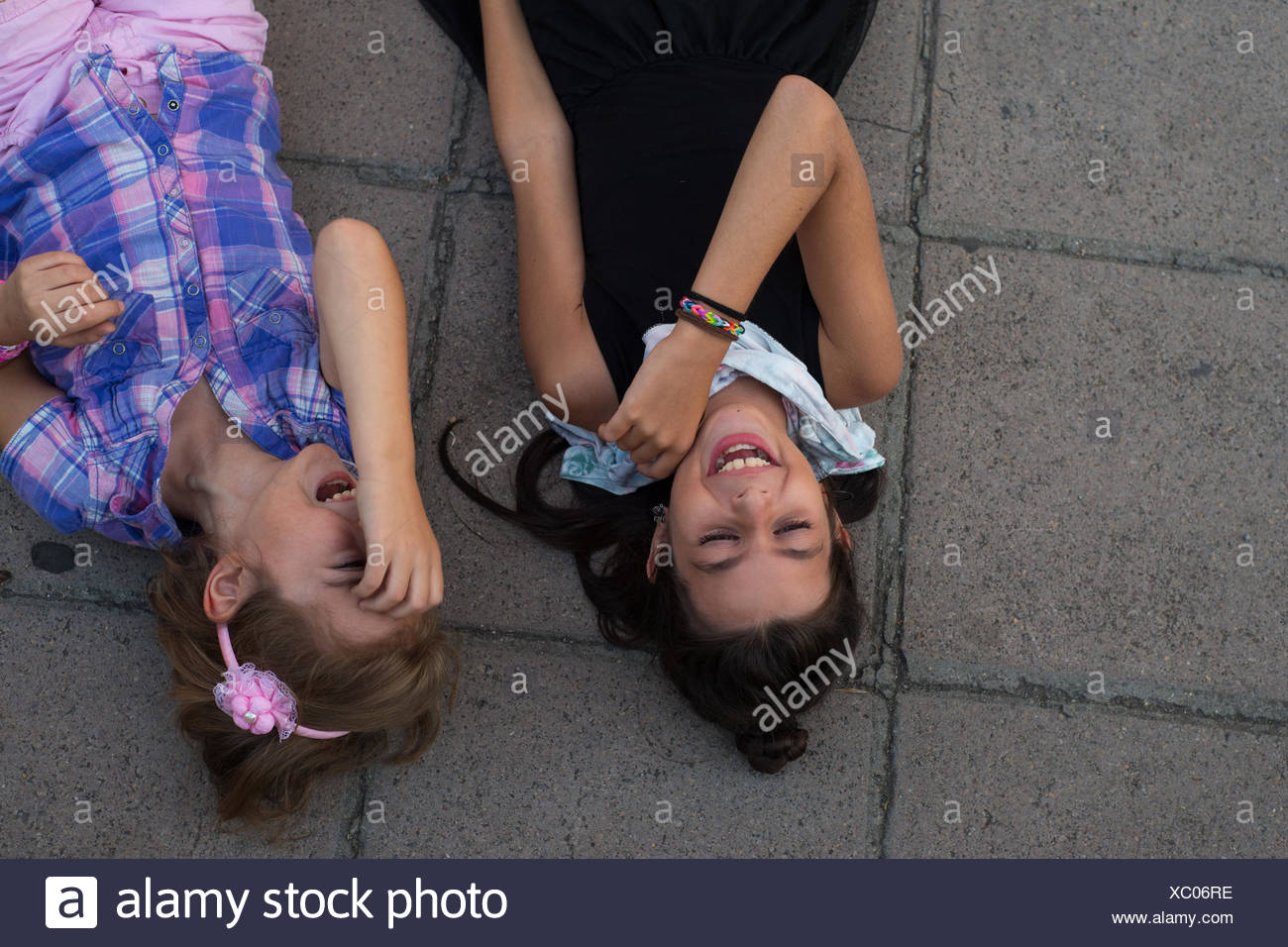 Two girls lying on ground laughing Stock Photo