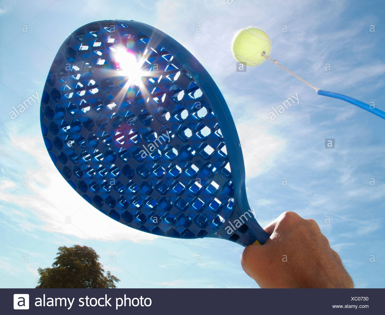 Sun shining behind paddle hitting tennis ball - Stock Image