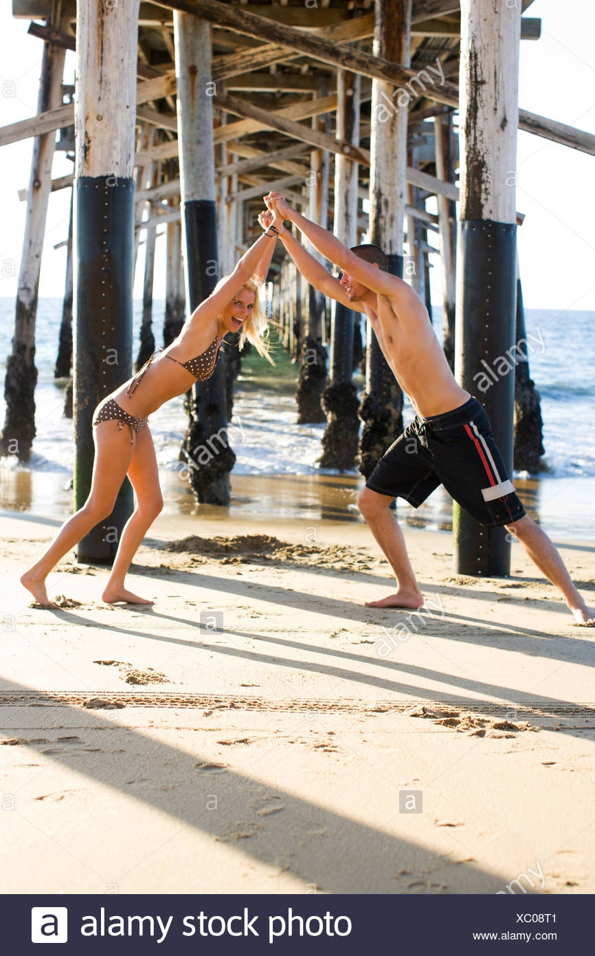 A young couple in bathing suits frolic under a pier at the beach on a sunny afternoon in Newport Beach, California. - Stock Image