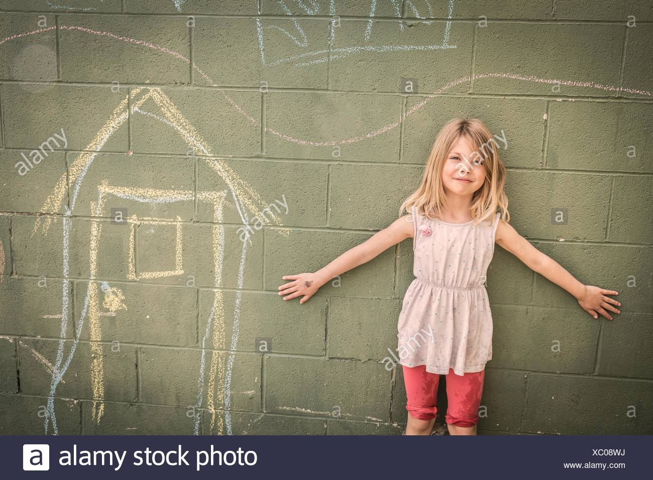Girl in front of wall with chalk drawings, portrait - Stock Image