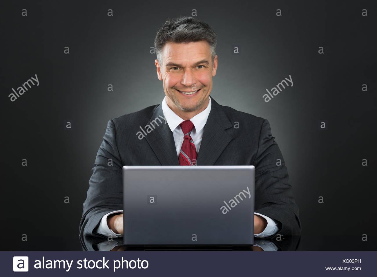 Businessman Working On Laptop At Desk - Stock Image