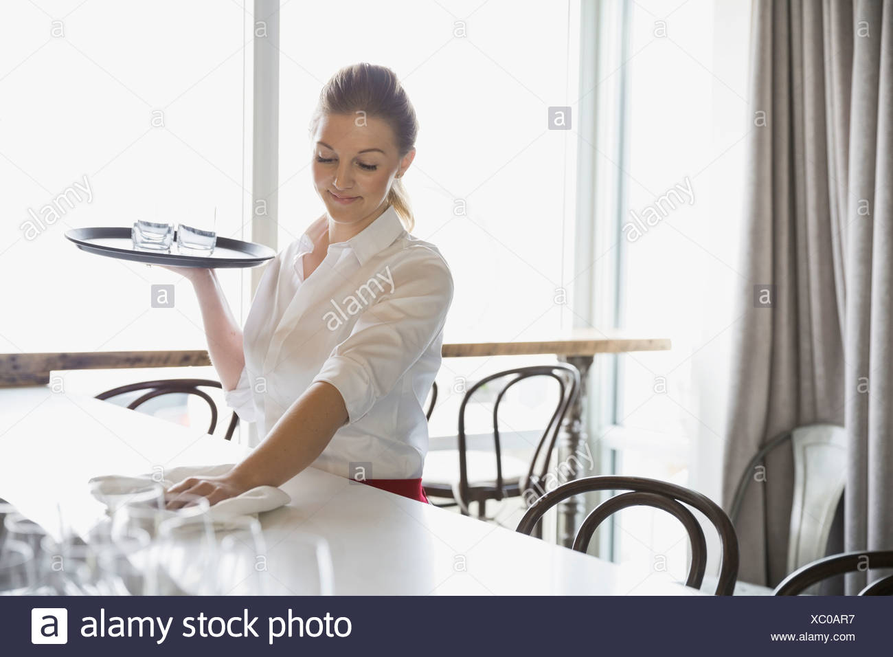 Waitress wiping counter in bistro - Stock Image
