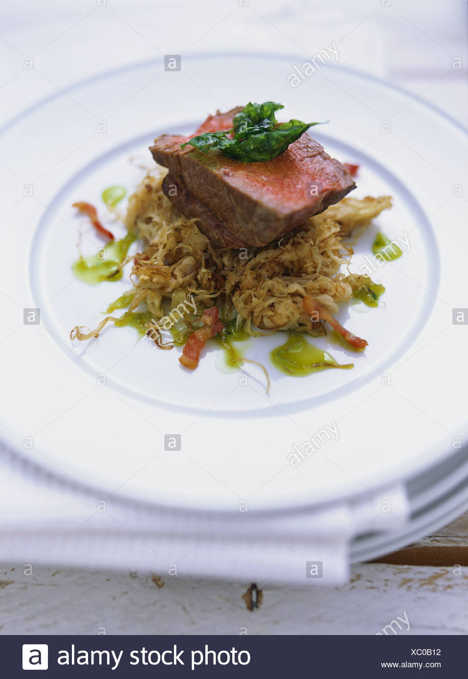 Medium-rare fillet of fattened ox on sauerkraut with grapes - Stock Image