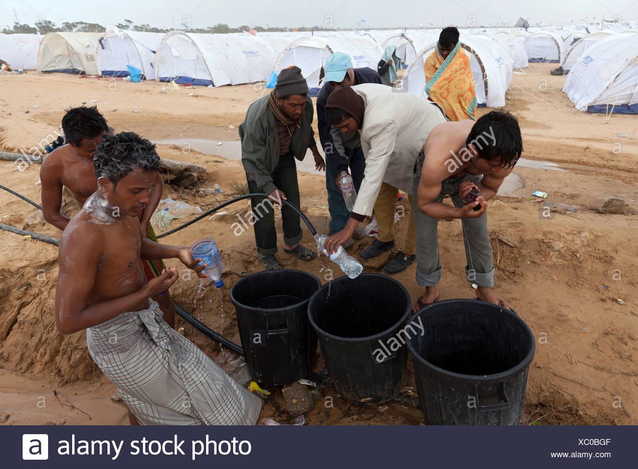 Bangladeshi washing themselves in the Shousha refugee camp, Ben Gardane, Tunisia - Stock Image