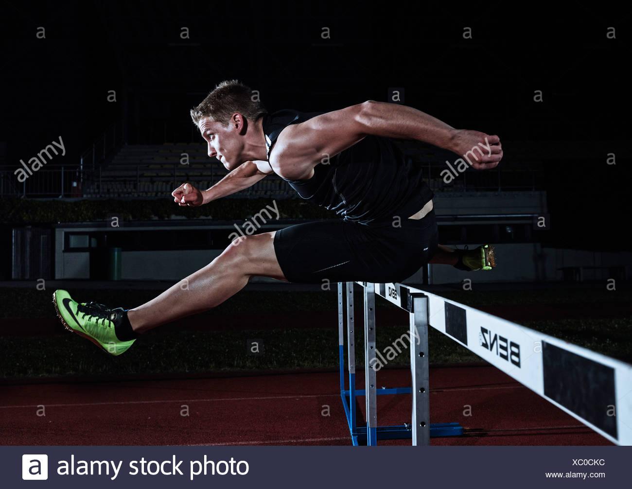 Hurdle racing athlete - Stock Image