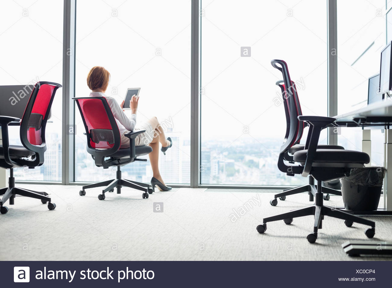 Full length of young businesswoman using tablet PC on chair in office - Stock Image