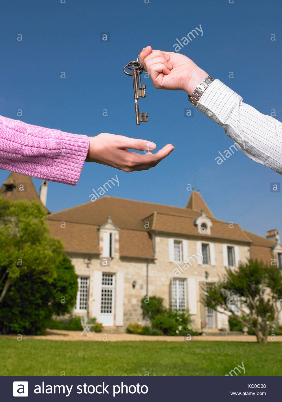 Woman receiving keys to country home - Stock Image