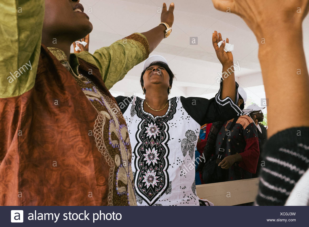 Women sing praise songs near the River Jordan, where devotees come to visit the place where Jesus is believed to have been baptized. - Stock Image
