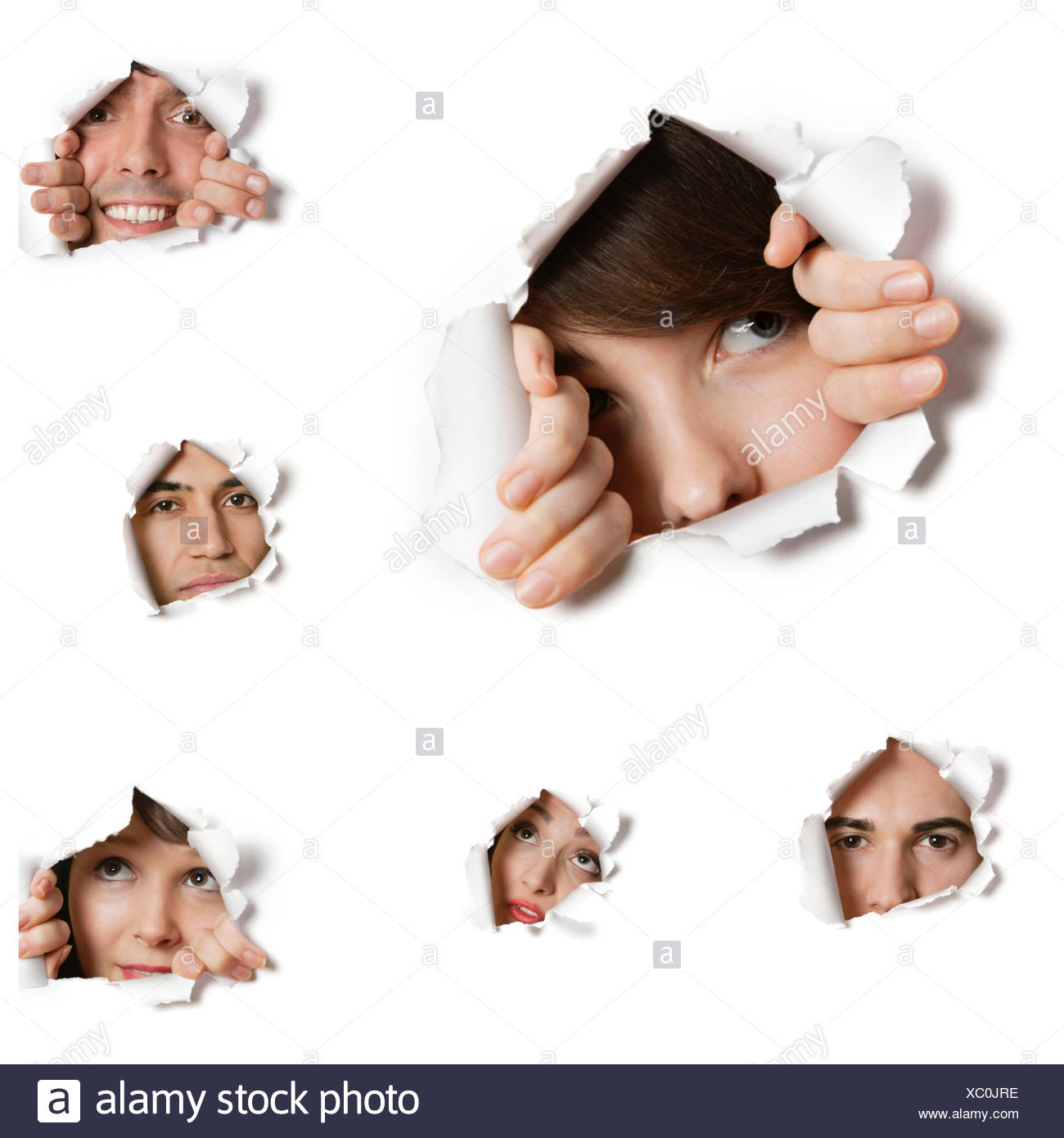 Multiethnic people looking through ripped paper holes - Stock Image