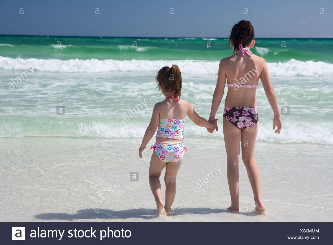 Two little girls in bikinis are holding hands at shoreline with the ocean in the background. - Stock Image