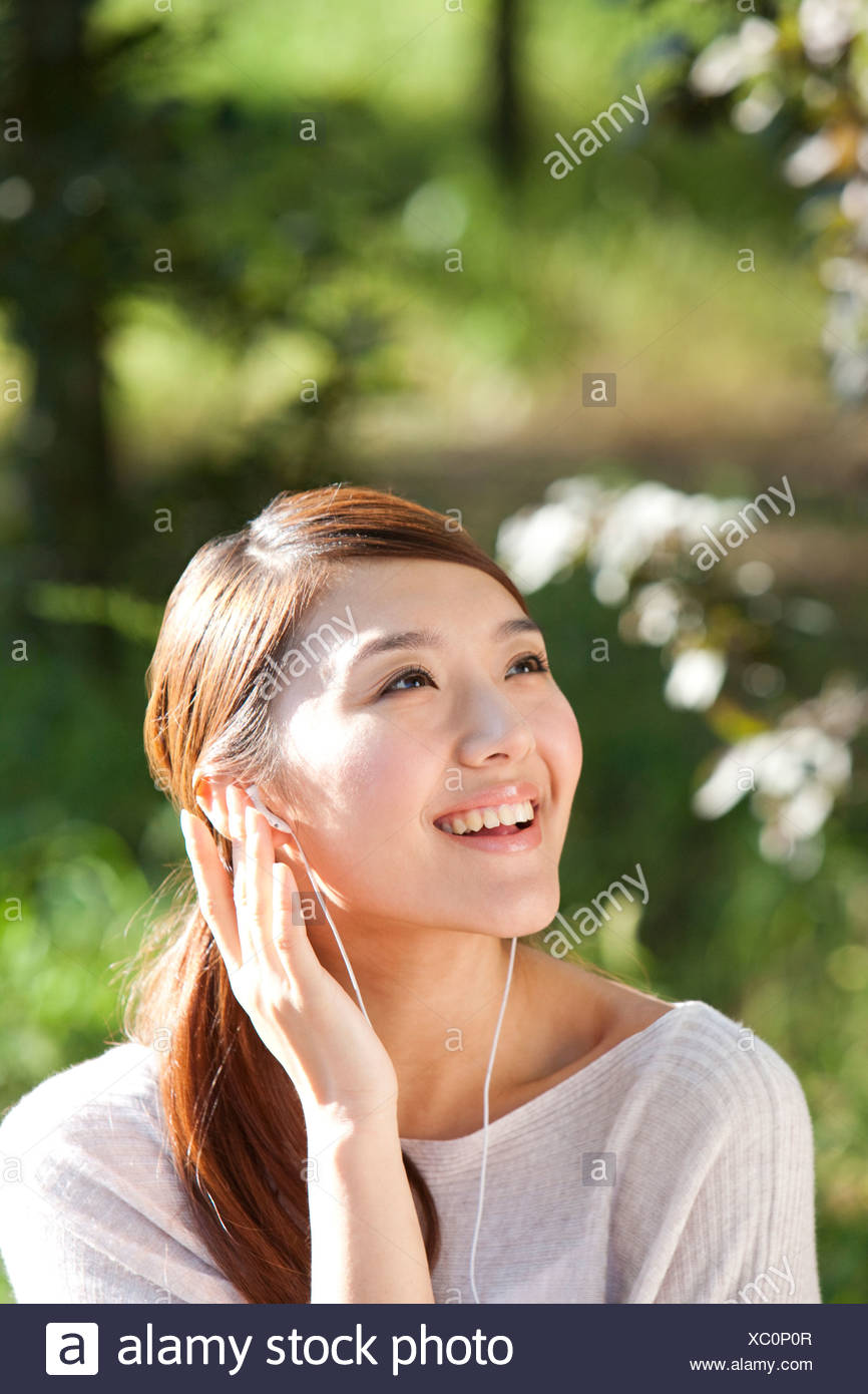 Young Chinese woman outdoors listening to music - Stock Image