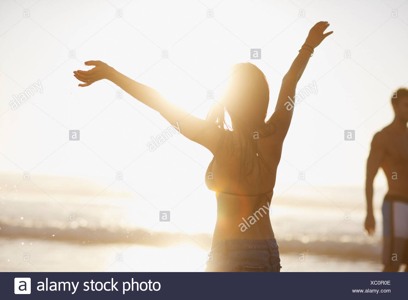 Woman in bikini cheering on beach Stock Photo