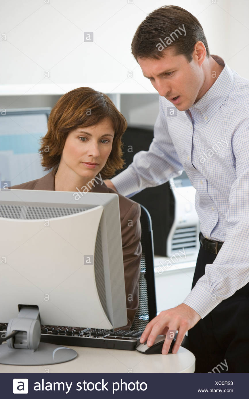 Businesswoman and businessman looking at computer - Stock Image