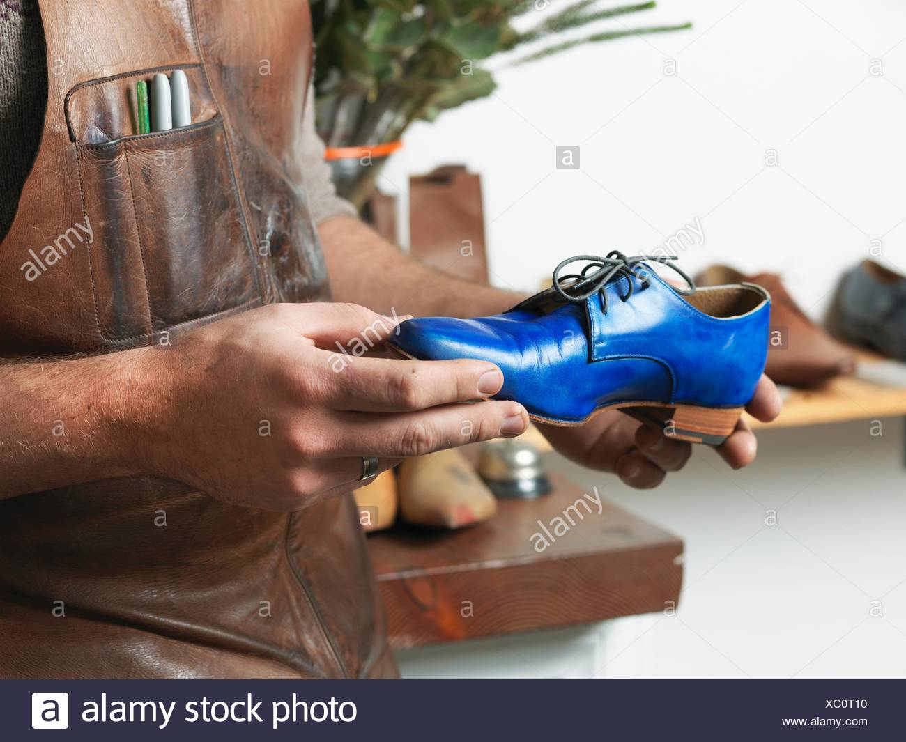 Shoemaker holding blue shoe in workshop - Stock Image