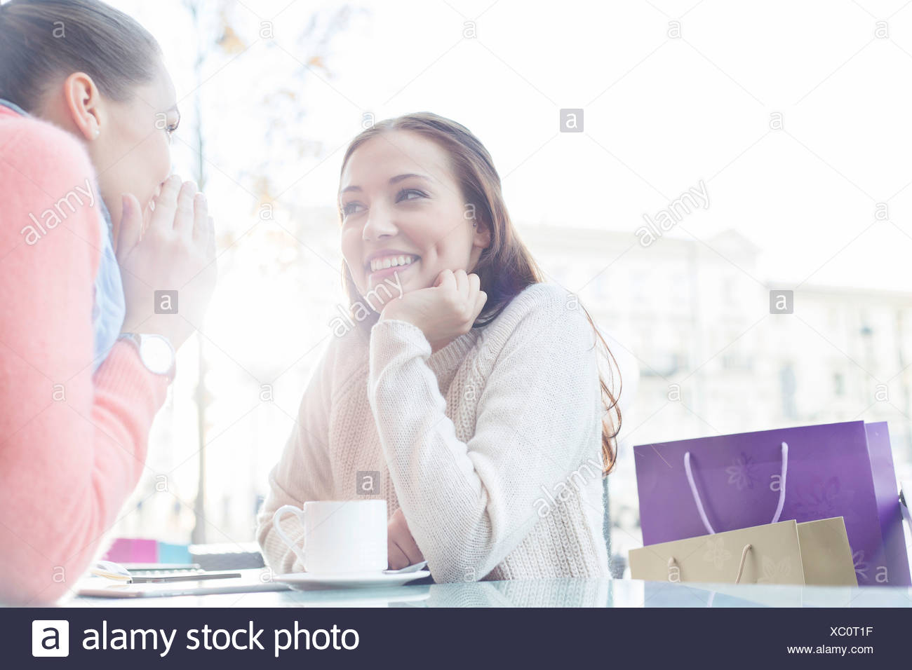 Beautiful young woman looking at friend sharing secrets at outdoor cafe - Stock Image
