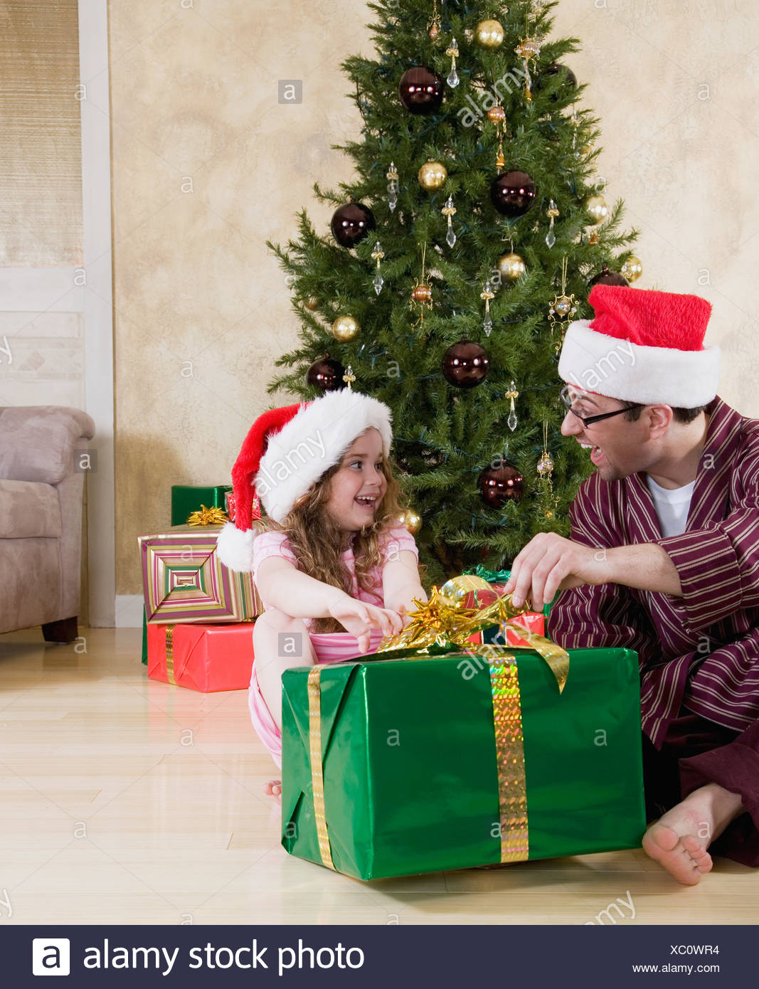 Father and daughter (5-6) in Santa hats opening Christmas present - Stock Image