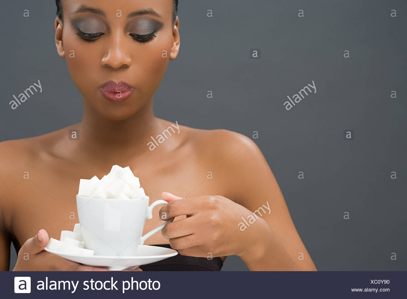 Woman holding a cup of sugar lumps - Stock Image