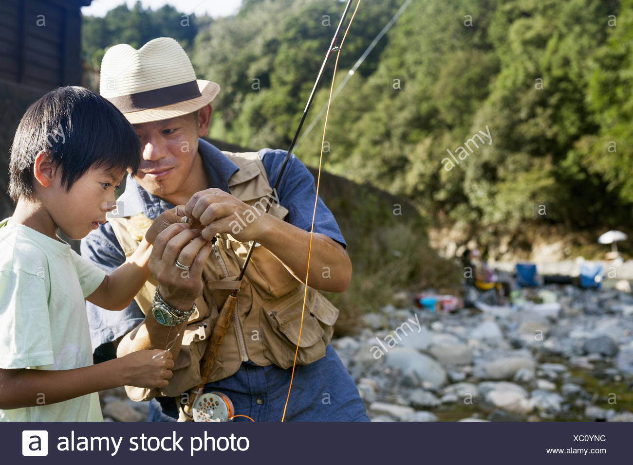 Father and son fishing by a stream. - Stock Image