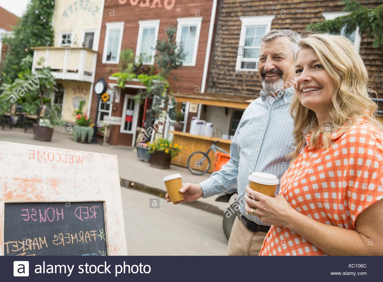 Couple enjoying coffee outside cafe - Stock Image