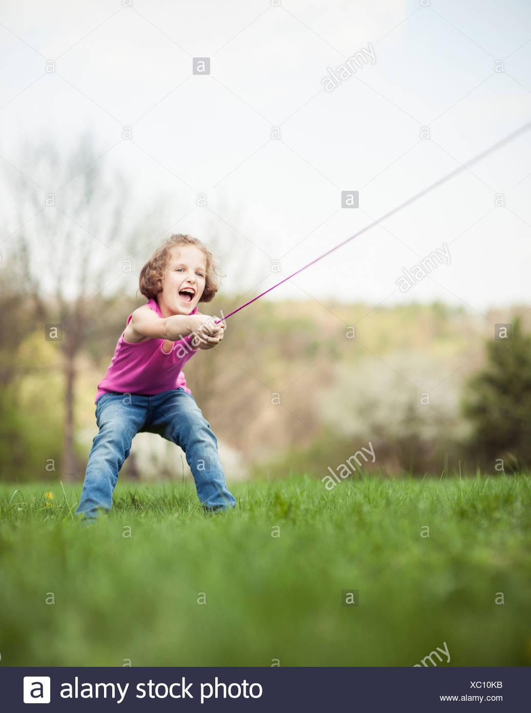 Young girl playing tug of war - Stock Image