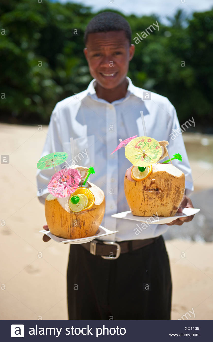 A waiter holding two decorated coconuts filled with drinks, island Mahe, Seychelles, Indian Ocean, Africa - Stock Image