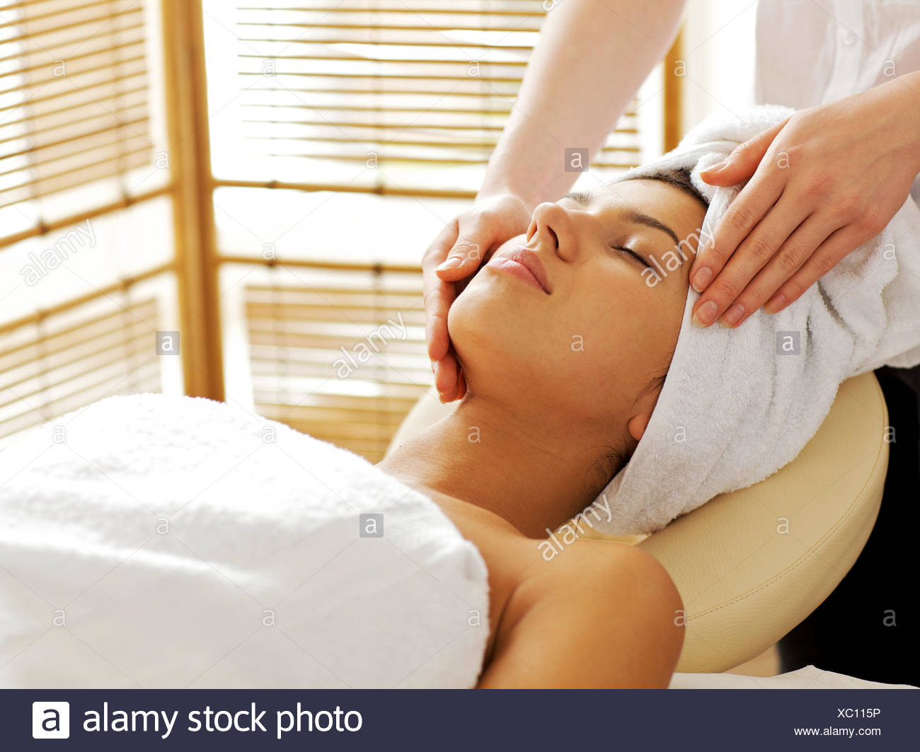Young woman receiving facial massage, eyes closed Stock Photo