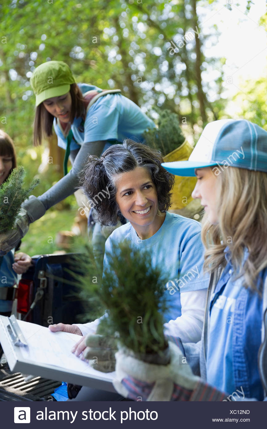 Smiling leader with clipboard guiding tree planting volunteer - Stock Image