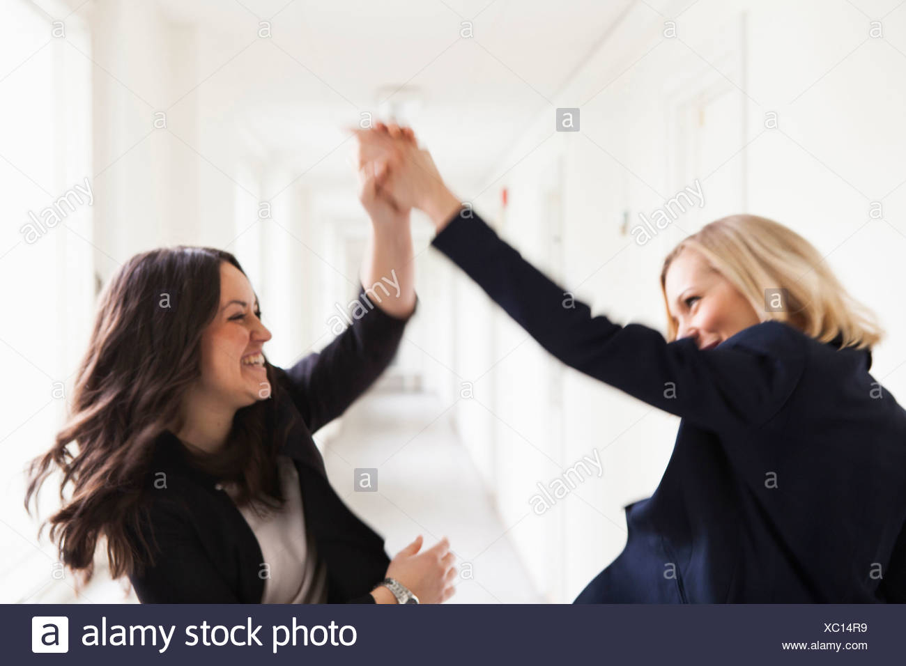 Successful businesswomen giving high-five in office - Stock Image