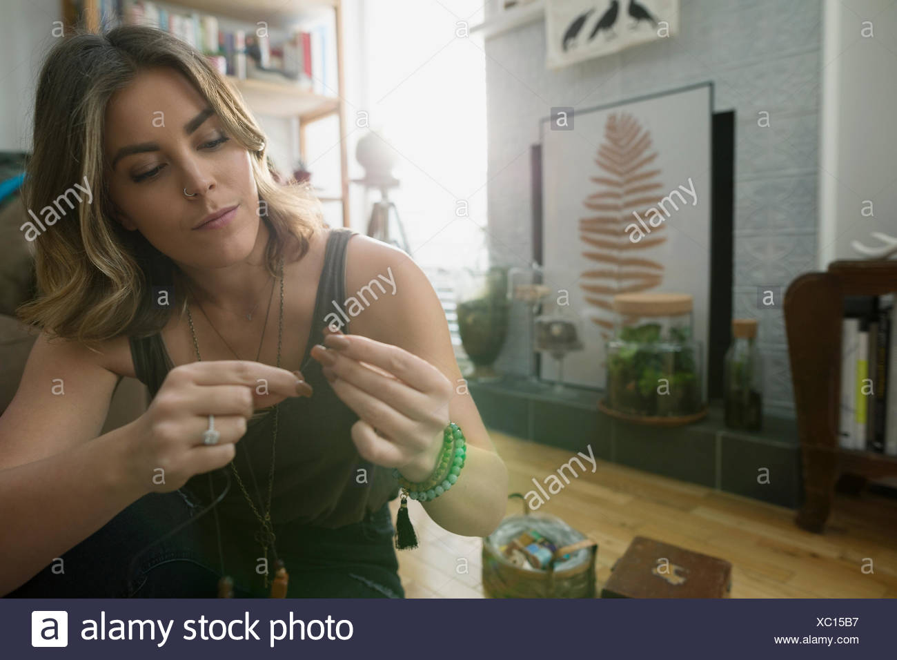 Focused woman making jewelry in living room - Stock Image