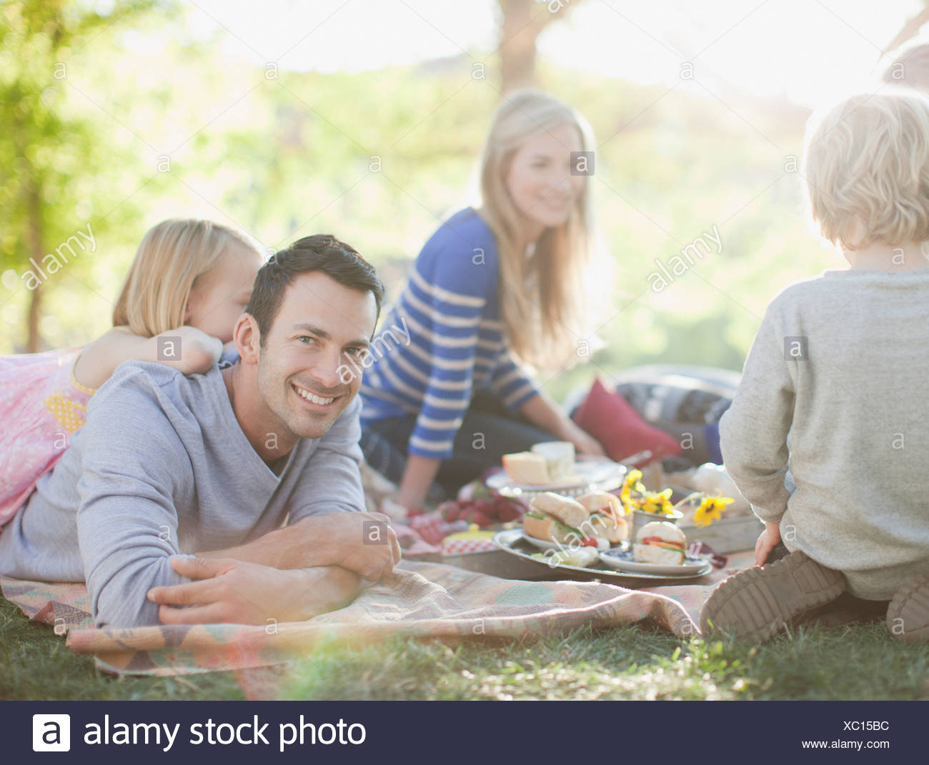 Family picnicking together on grass - Stock Image