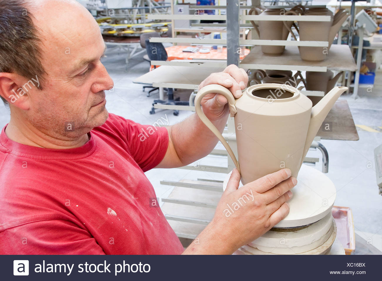 Employees attaching a handle, coffee pot from Hutschenreuther, in the production of tableware at the porcelain manufacturer - Stock Image