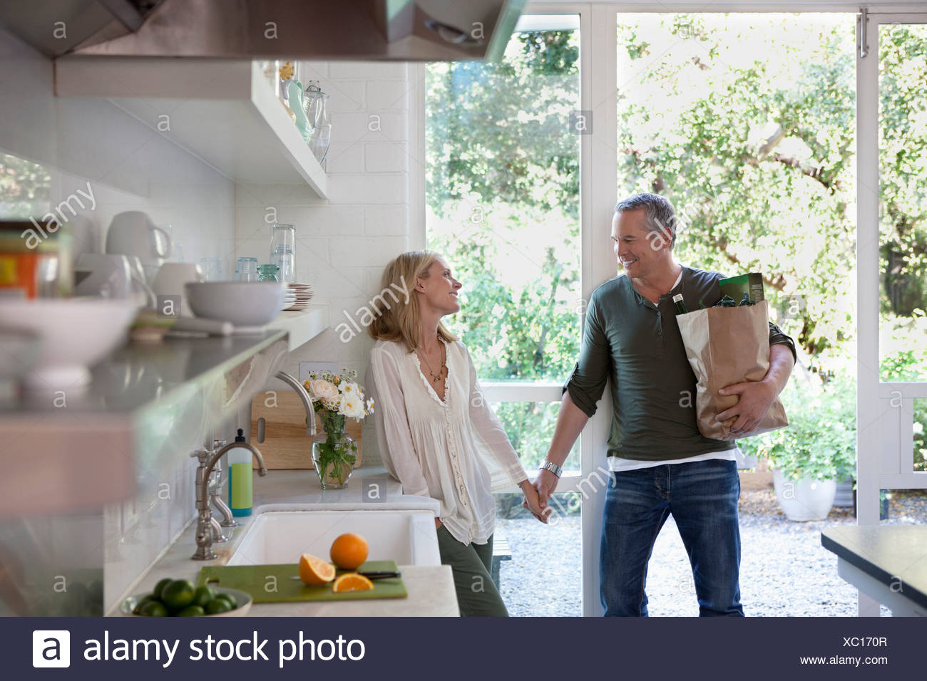 Couple holding hands in kitchen Stock Photo