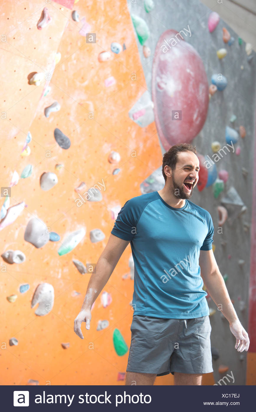 Dedicated man shouting by climbing wall in crossfit gym - Stock Image